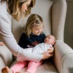 big sister holding newborn
